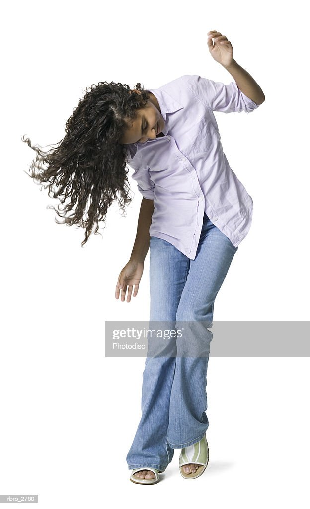 full length shot of a teenage female as she playfully dances and tosses her hair around : Foto de stock