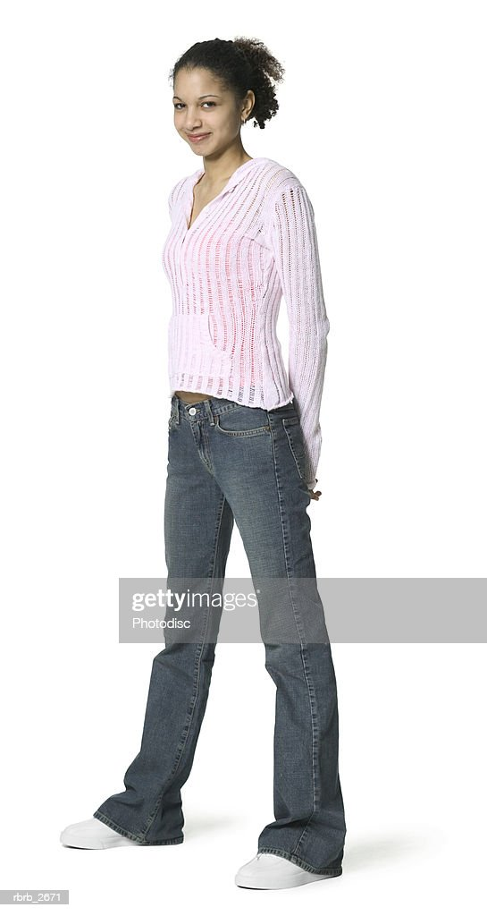 full length shot of a teenage female in a pink sweater as she smiles at the camera : Foto de stock