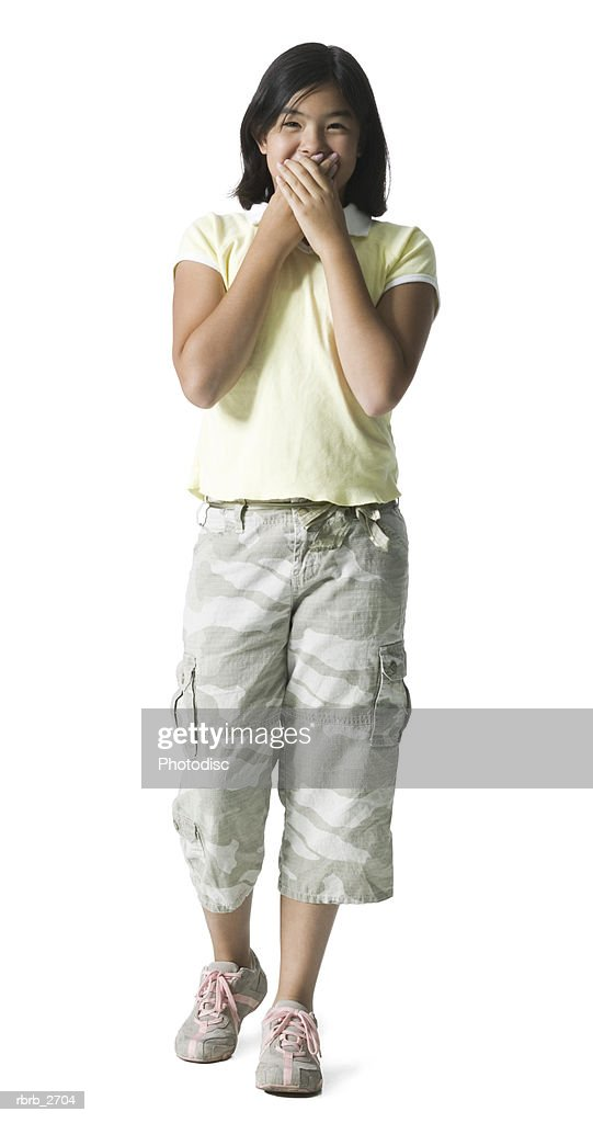 full length shot of a teenage female in a yellow shirt as she act surprised : Foto de stock