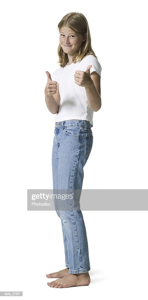 full length shot of a teenage female in jeans and a white shirt as she gives the thumbs up : Foto de stock