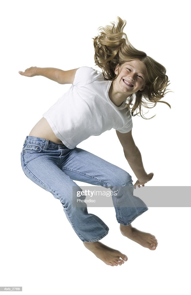 full length shot of a teenage female in jeans and a white shirt as she jumps up : Foto de stock