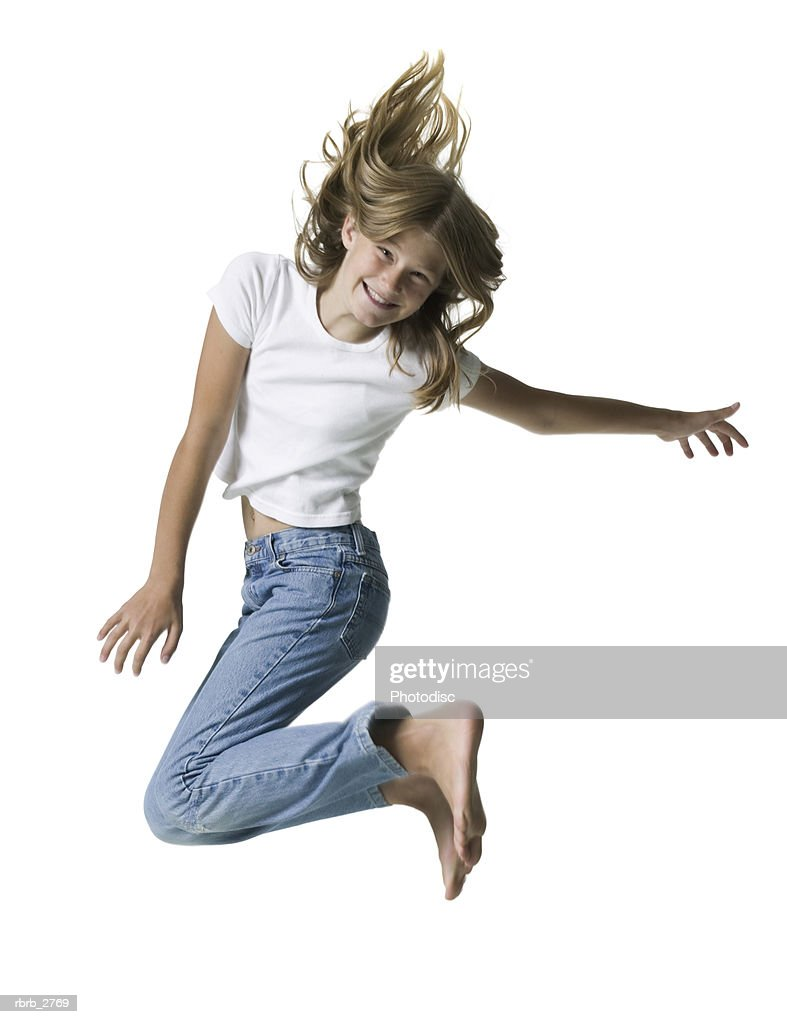 full length shot of a teenage female in jeans and a white shirt as she jumps through the air : Foto de stock
