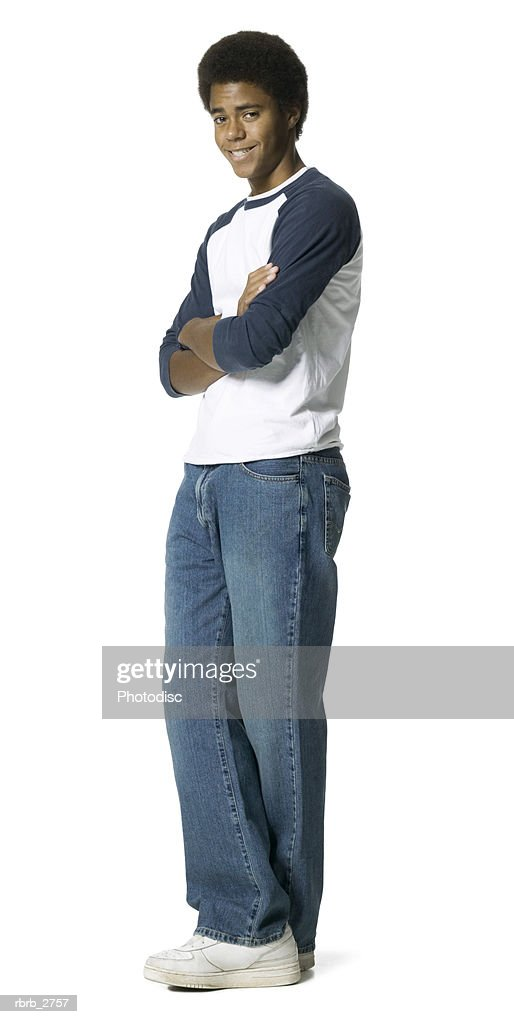 full length shot of a teenage male in a blue and white shirt as he turns and smiles : Foto de stock