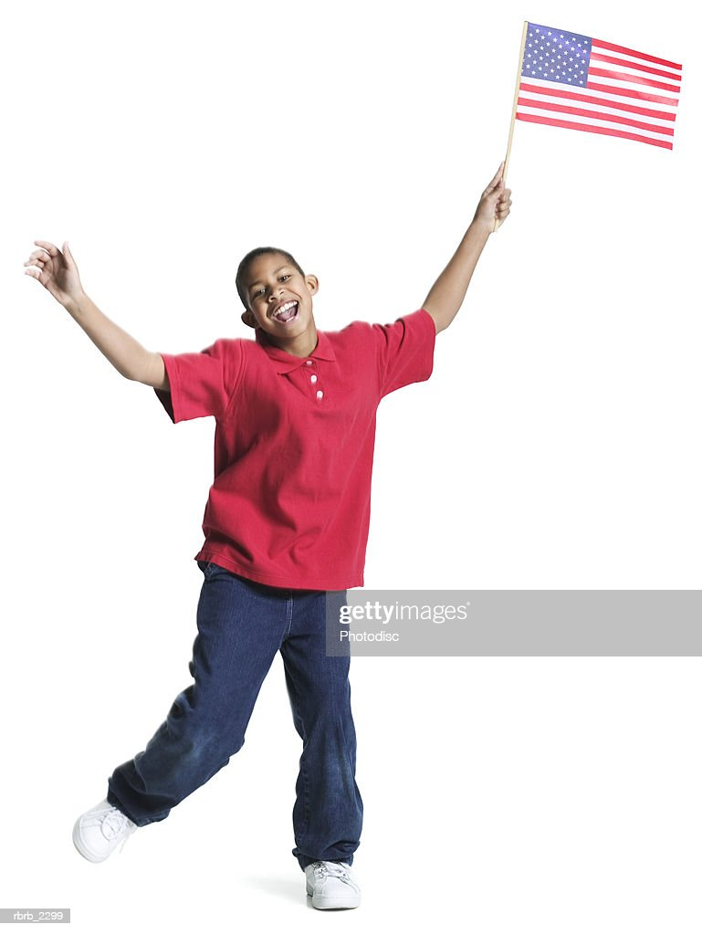 full length shot of a teenage male in a red shirt as he jumps up waving an american flag : Foto de stock