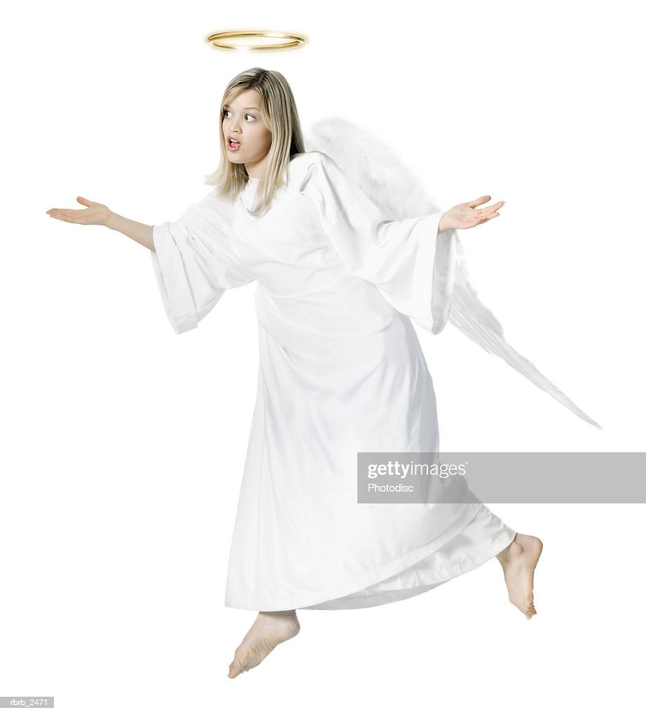 full length shot of a young adult female angel as she float through the air with her wings : Stockfoto
