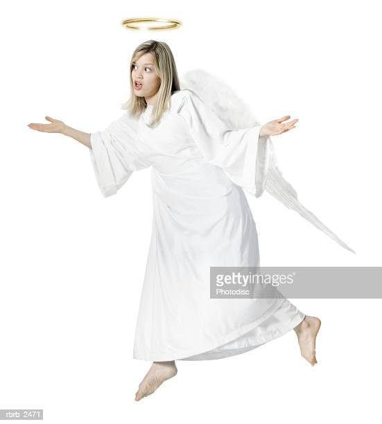 full length shot of a young adult female angel as she float through the air with her wings