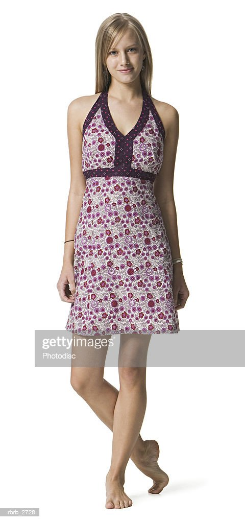 full length shot of a young adult female in a printed dress as she looks at the camera : Foto de stock