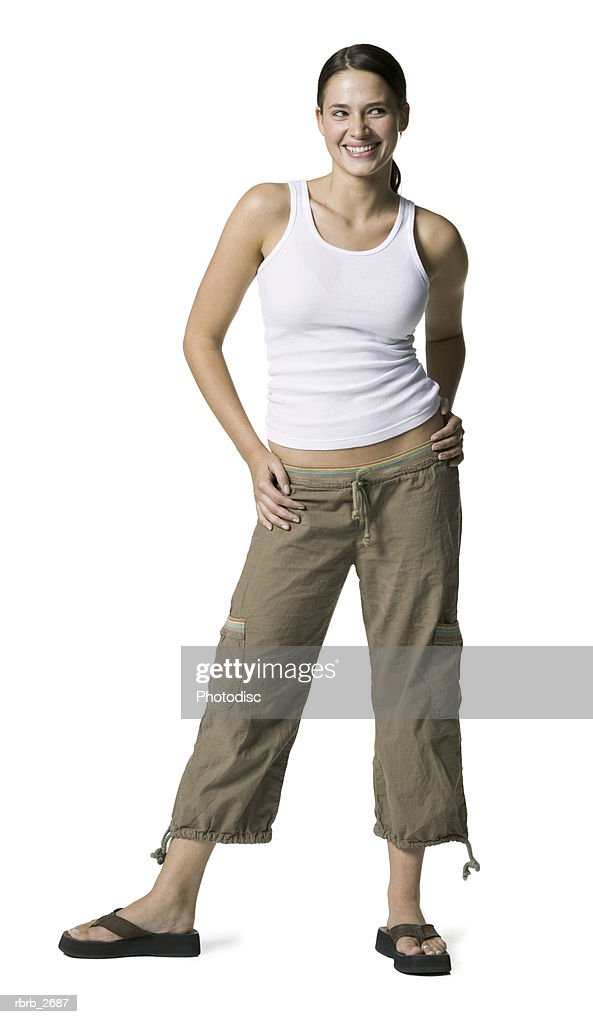 full length shot of a young adult female in a white tank top as she smiles and glances upward : Foto de stock