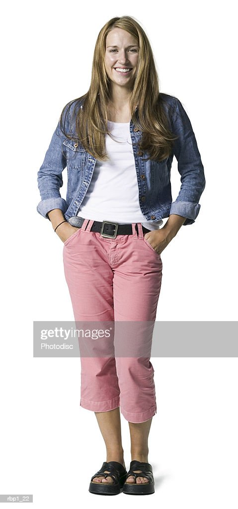 full length shot of a young adult female in  pink pants and jean jacket as she smiles at the camera : Stockfoto