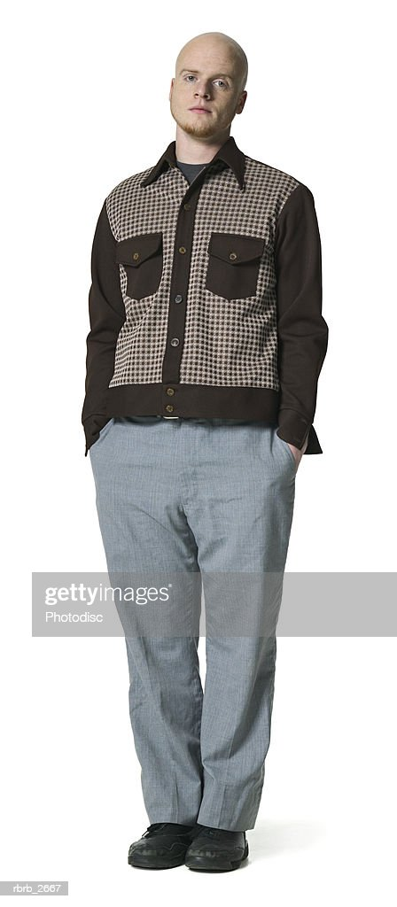 full length shot of a young adult male as he puts his hands in his pockets and glares at the camera : Foto de stock