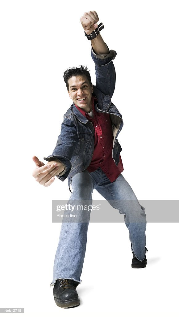 full length shot of a young adult male in a jean jacket as he playfully moves around : Foto de stock