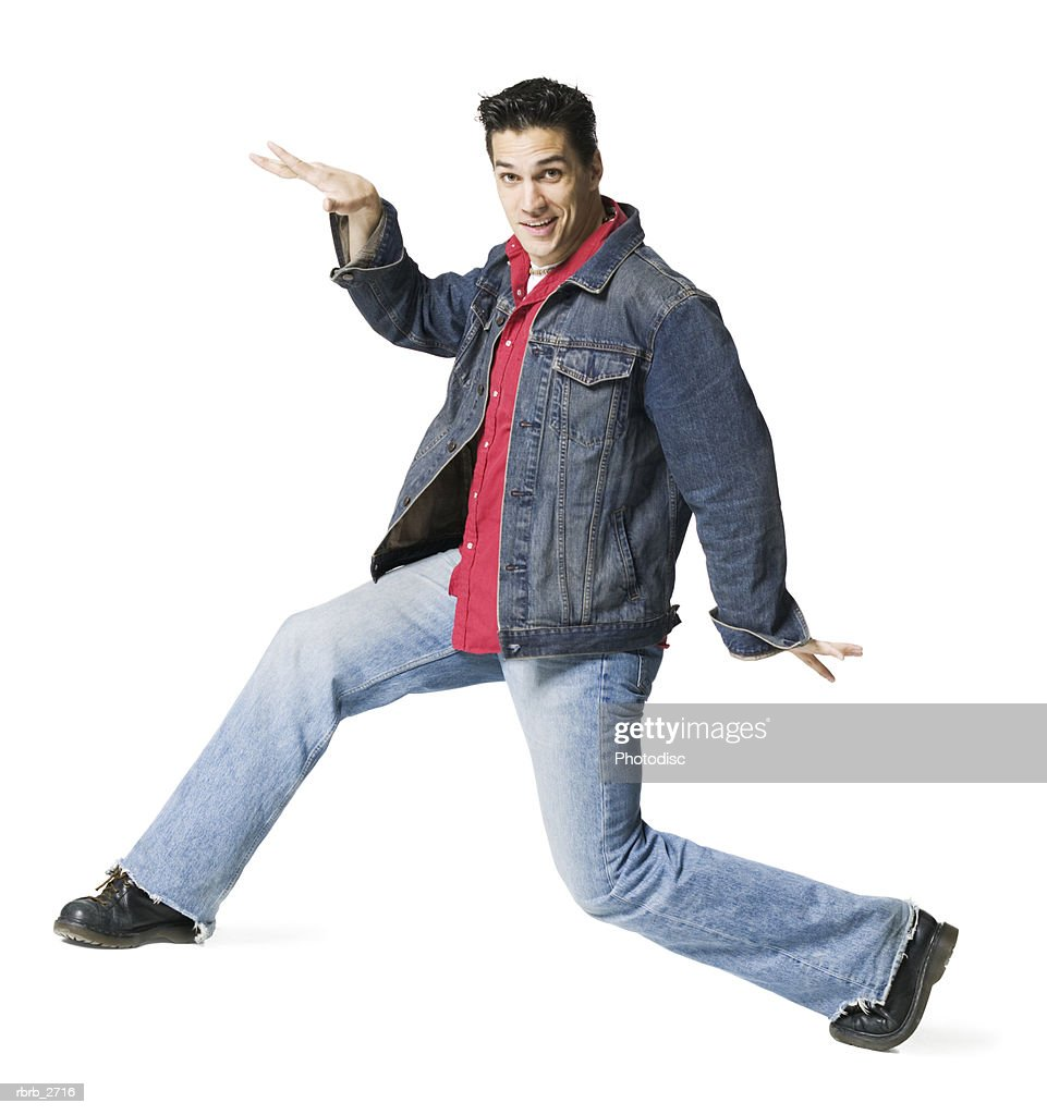 full length shot of a young adult male in a jean jacket as he strikes a fun pose : Foto de stock