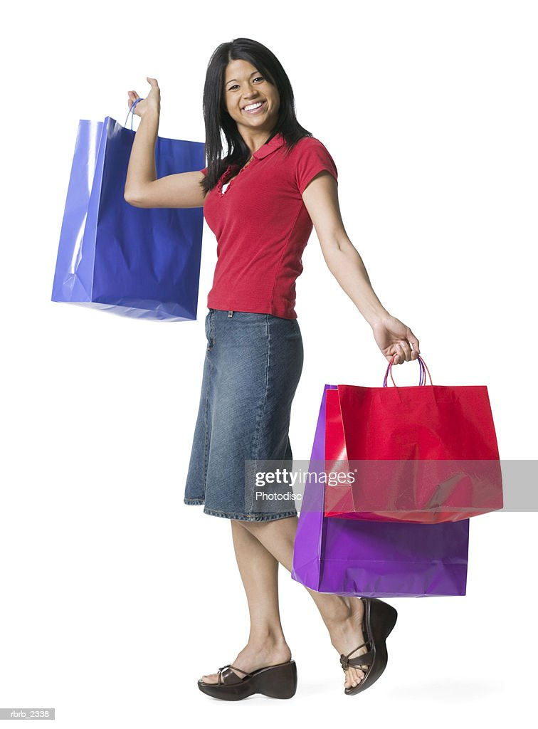 full length shot of a young adult woman as she playfully holds up numerous shopping bags : Foto de stock