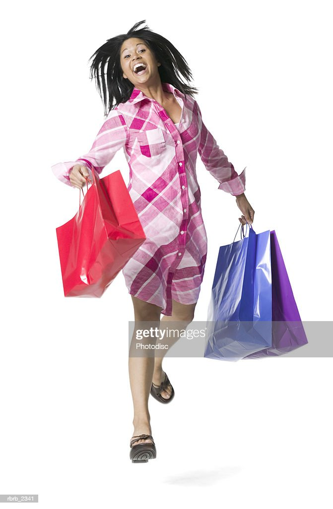 full length shot of a young adult woman as she runs with numerous shopping bags : Foto de stock