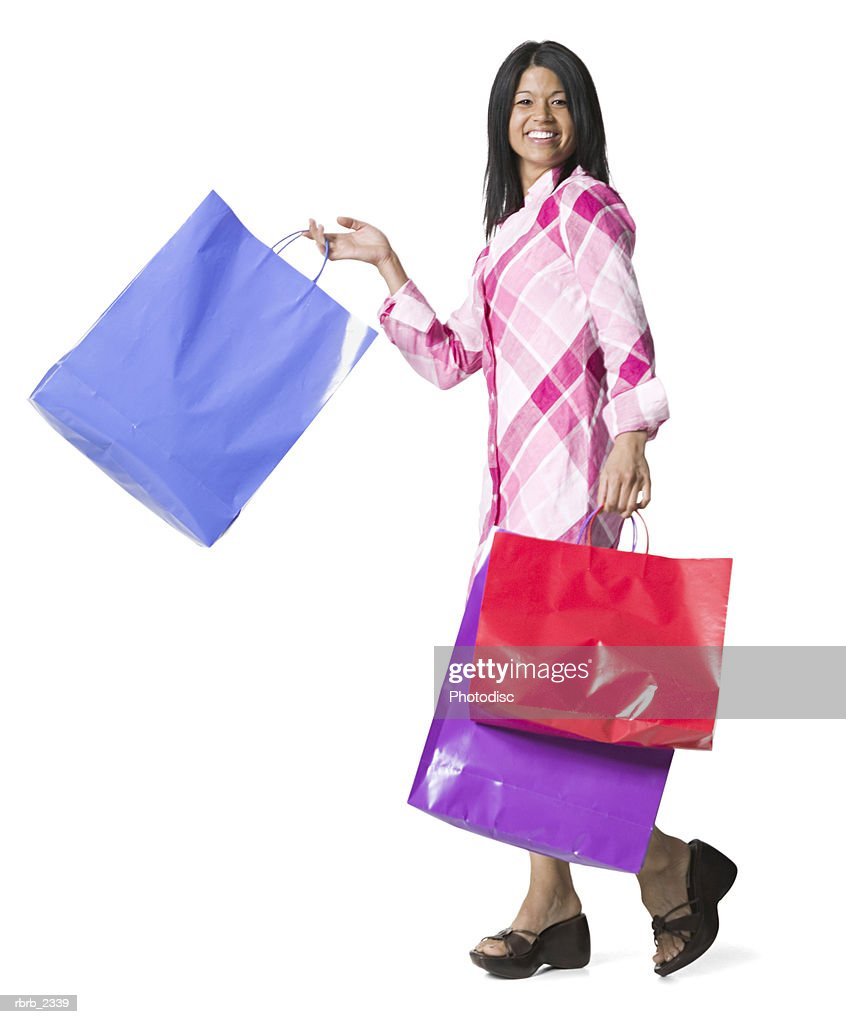 full length shot of a young adult woman as she walks and swings her shopping bags : Foto de stock
