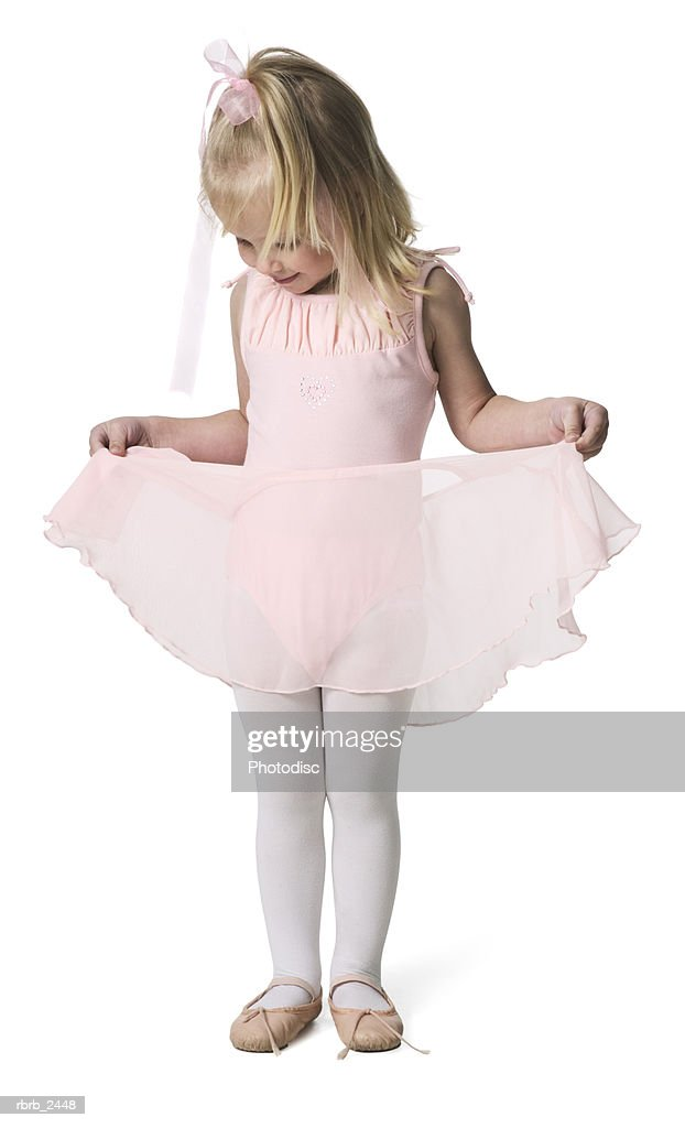 full length shot of a young female child in a pink ballet outfit as she plays with her tutu : Foto de stock