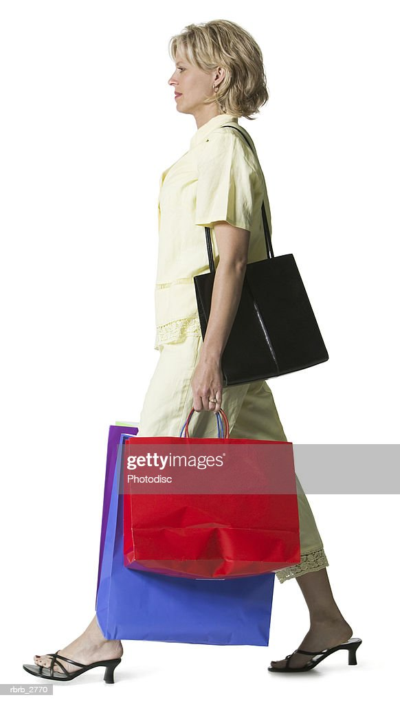 full length shot of an adult blonde woman in a yellow dress as she walks with shopping bags : Foto de stock