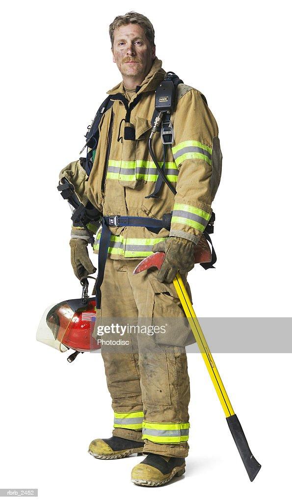 full length shot of an adult male fireman in his gear as he smiles : Foto de stock