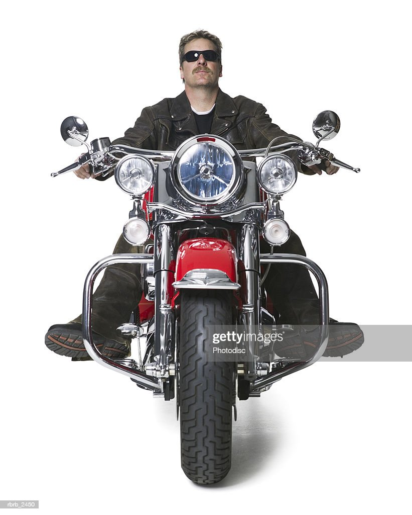 full length shot of an adult male in leather and sunglasses as he sits atop his motorcycle : Stockfoto