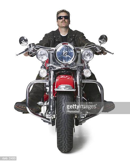 full length shot of an adult male in leather and sunglasses as he sits atop his motorcycle