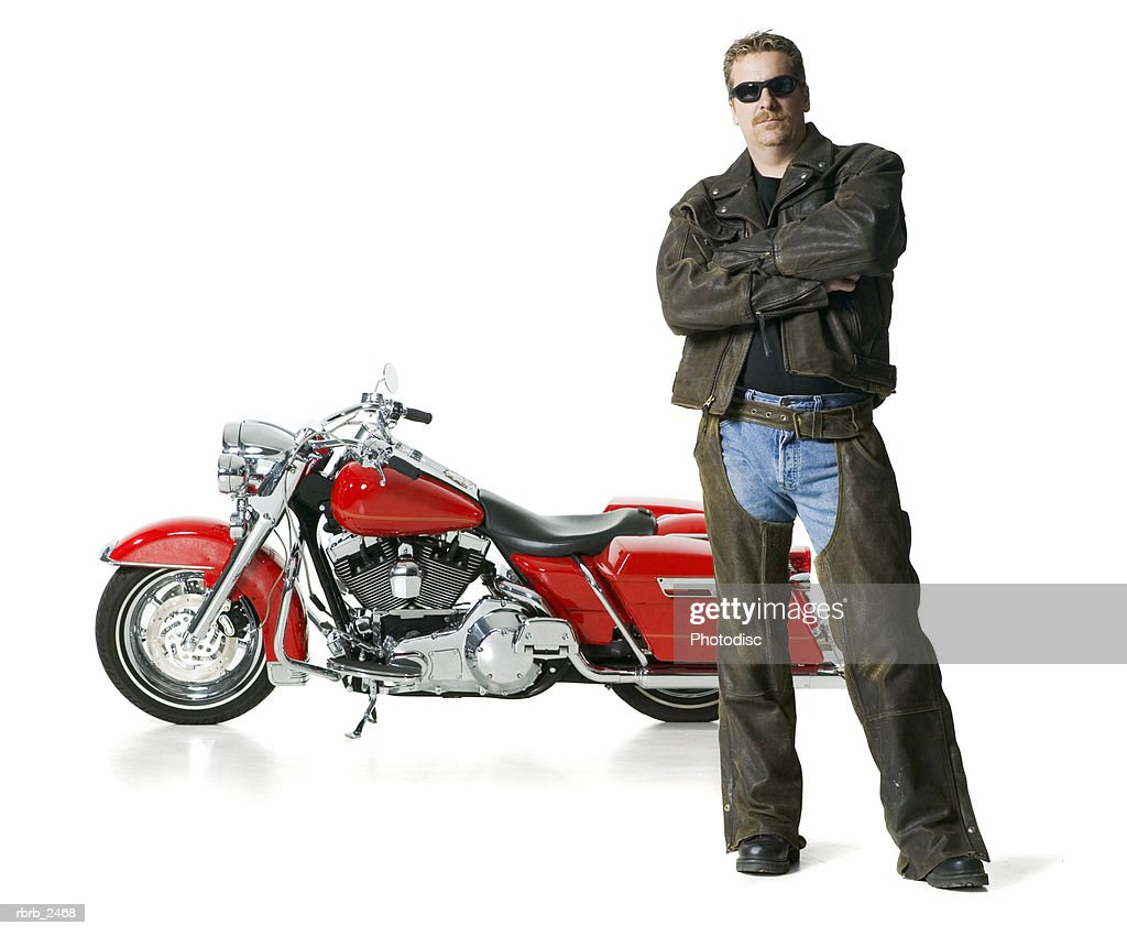 full length shot of an adult male in leather and sunglasses as he stands with his bike : Foto de stock
