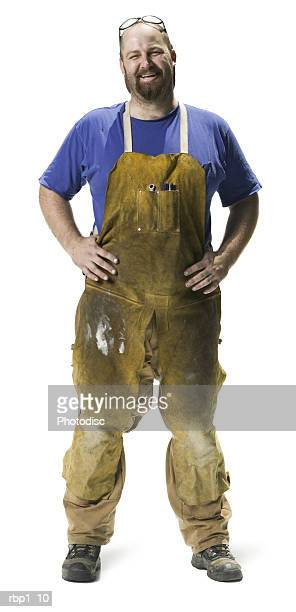 full length shot of an adult male in work overalls as he smiles at the camera - bib overalls stock pictures, royalty-free photos & images