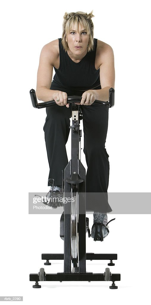 full length shot of an adult woman in a black workout outfit as she uses an exercise bike : Foto de stock