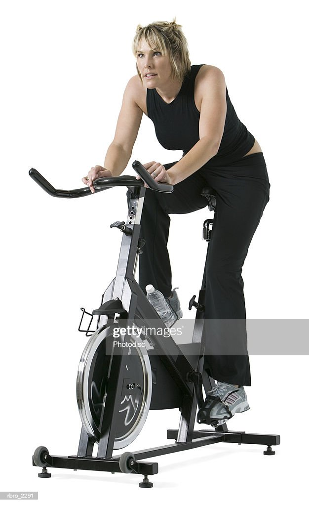 full length shot of an adult woman in a black workout outfit as she rides an exercise bike : Foto de stock