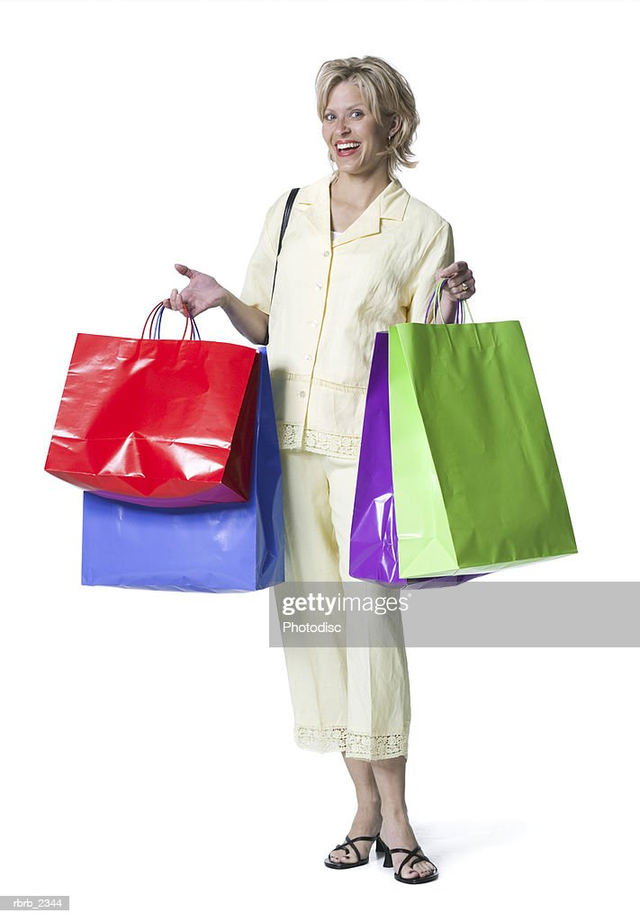 full length shot of an adult woman in a yellow dress as she holds up with shopping bags : Foto de stock