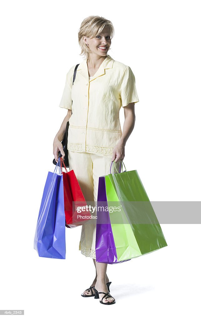 full length shot of an adult woman in a yellow dress as she stands with shopping bags : Stockfoto