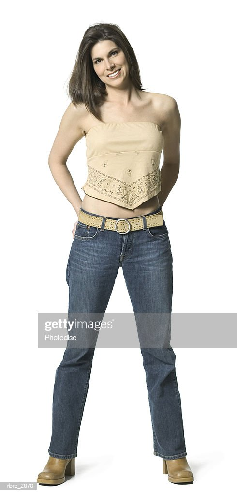 full length shot of an attractive adult female in a tan shirt as she smiles at the camera : Foto de stock