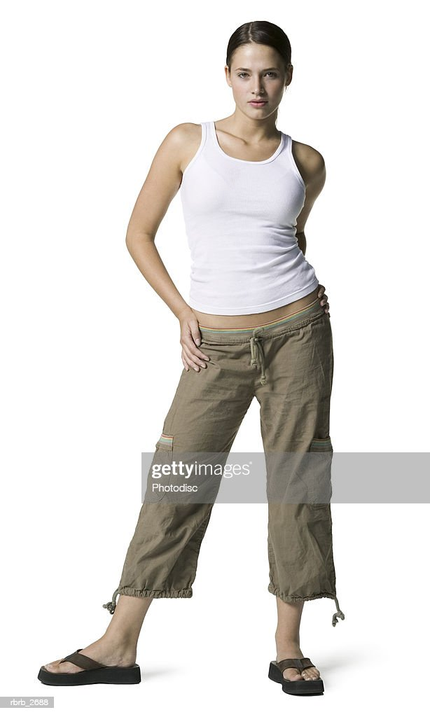 full length shot of an attractive young adult female in a white tank top as she looks at the camera : Foto de stock