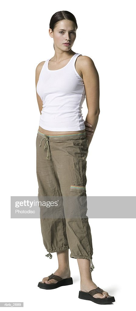 full length shot of an attractive young adult female in a white tank top as she shows some attitude : Foto de stock