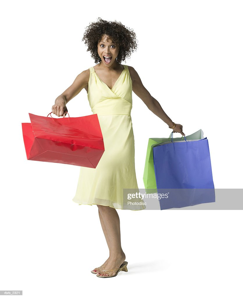 full length shot of an attractive young adult woman in a yellow dress as she runs with shopping bags : Foto de stock