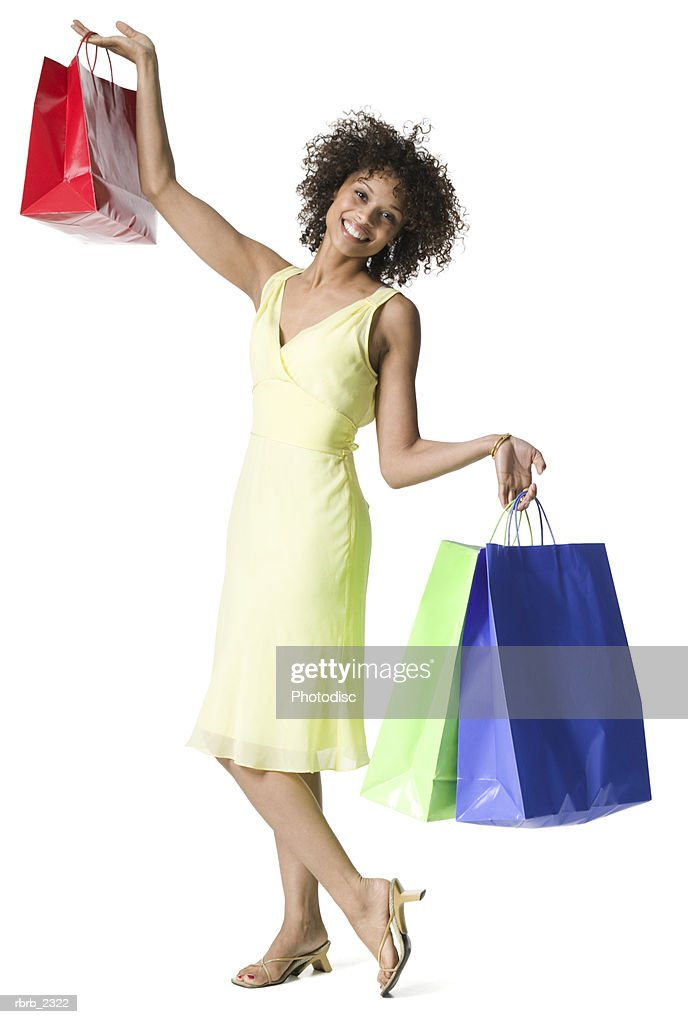 full length shot of an attractive young adult woman in a yellow dress as she holds up shopping bags : Foto de stock