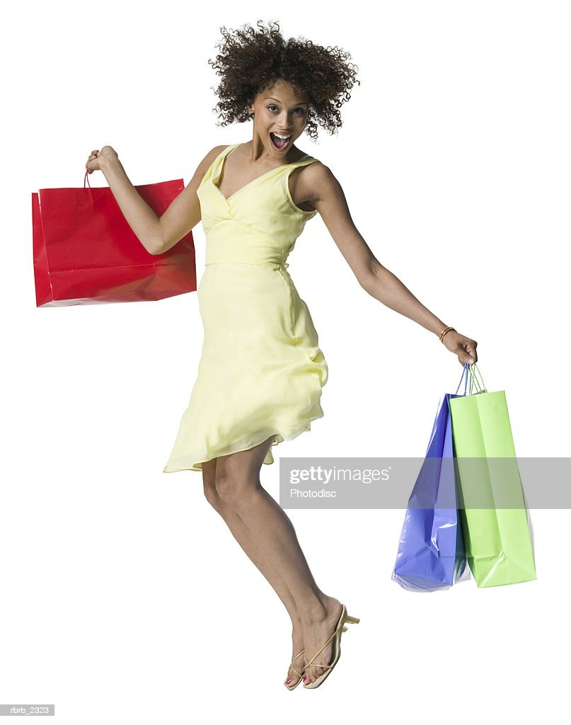 full length shot of an attractive young adult woman in a yellow dress as she jumps up with shopping bags : Foto de stock