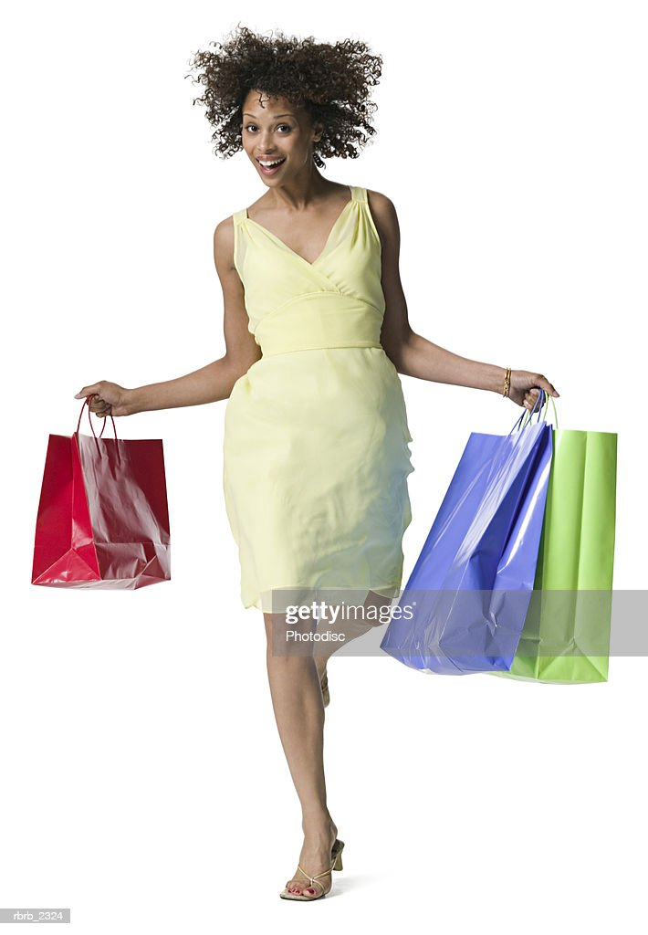 full length shot of an attractive young adult woman in a yellow dress she skips with shopping bags : Foto de stock