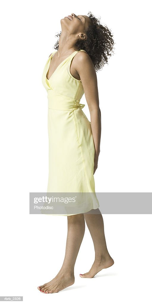 full length shot of an attractive young adult woman in a yellow dress as she glances upward : Foto de stock