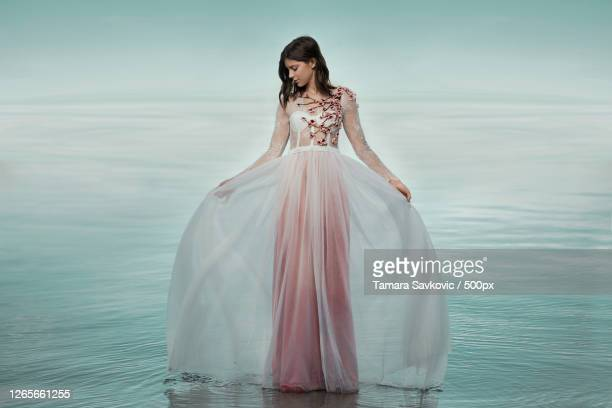 full length shot of beautiful young caucasian woman in dress standing on water, novi sad, serbia - images stock-fotos und bilder