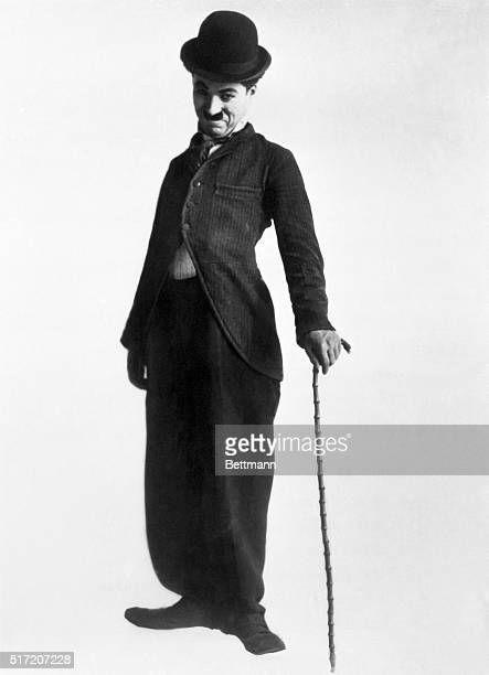 Full length shot of Charlie Chaplin in typical pose and attirelongtailed coat baggy trousers bowler hat slightly cocked bambu cane Undated photograph
