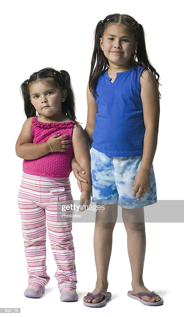 full length shot of two female child sisters as they stand together and smile at the camera : Stockfoto