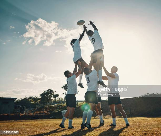 full length shot of two handsome young rugby players catching the ball during a lineout on the field - rugby stock pictures, royalty-free photos & images