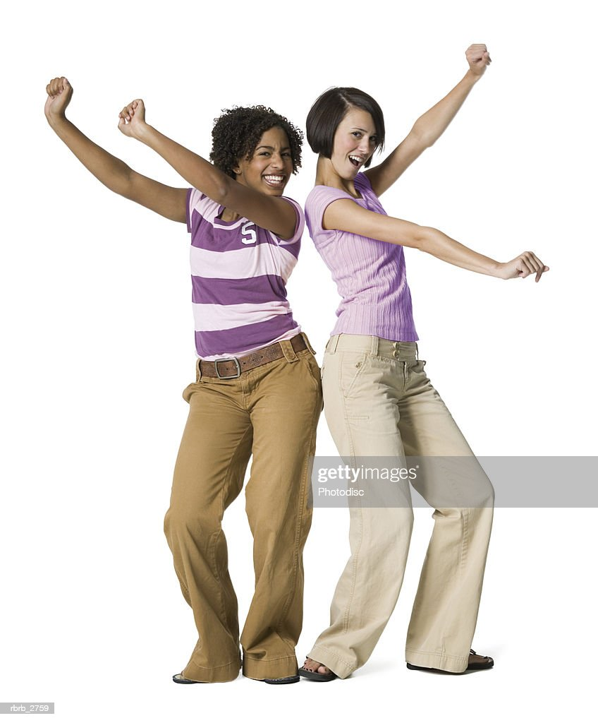 full length shot of two teenage female friends as they playfully dance around : Foto de stock