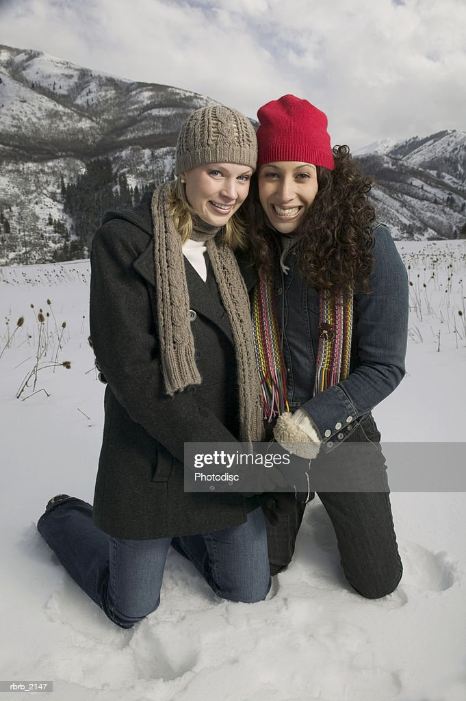 full length shot of two young adult women in winter clothing as they both kneel down in the snow : Stockfoto