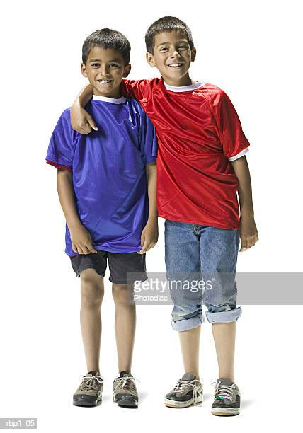 full length shot of two young brothers in blue and red shirts as they smile at the camera