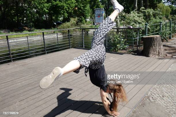 full length shot of young woman doing cartwheel - cartwheel stock pictures, royalty-free photos & images