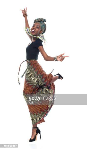 full length / side view of 20-29 years old african ethnicity / african-american ethnicity young women / female dancing / exercising in front of white background wearing headscarf / dress / traditional clothing who is smiling / happy / cheerful - 25 29 years stock pictures, royalty-free photos & images