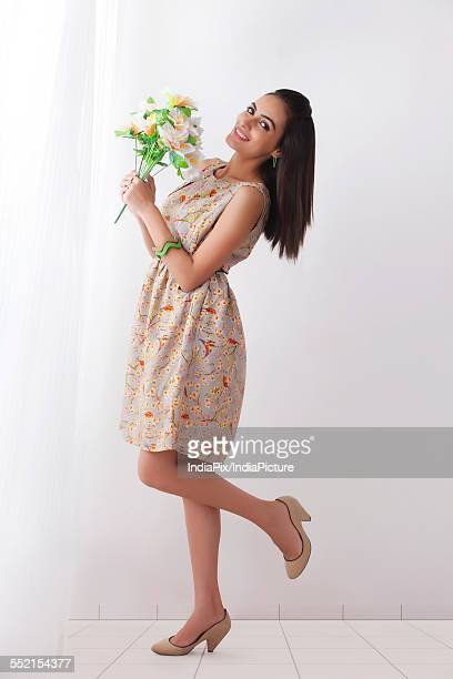 full length side view of beautiful young woman holding flowers by curtain - one young woman only stock pictures, royalty-free photos & images