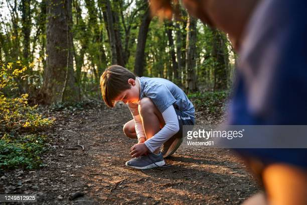 full length side view of boy crouching while tying shoelace in forest - tying shoelace stock pictures, royalty-free photos & images