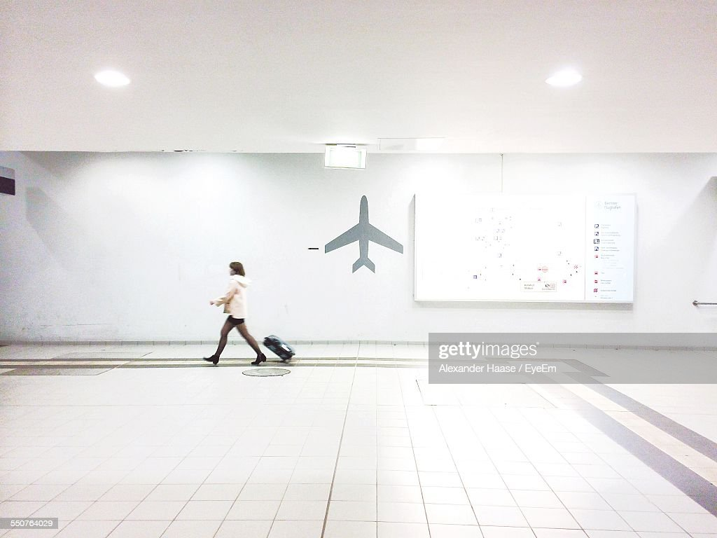 Full Length Side View Of Businesswoman With Luggage Walking In Airport Terminal : Stock Photo